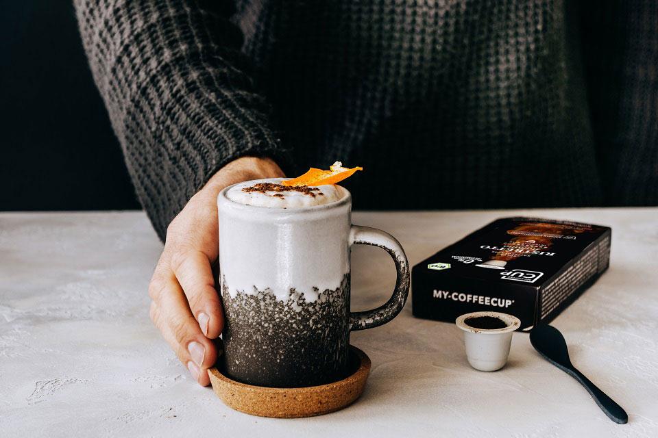 Eine wärmende Tasse Kaffee mit Milchschaum und Kakaoverzierung steht auf dem Tisch neben einer Papierschachtel mit den kompostierbaren Kaffeekapseln von My CoffeeCup, während eine Hand die Tasse festhält.
