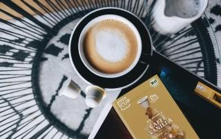 Von oben blickt man auf einen Glastisch, durch den man den schwarz-weiß gemusterten Teppich auf einem Holzboden sieht. Auf diesem Tisch steht eine Tasse mit dem Cafe Vanilla von My Coffee Cup mit Arabicabohnen in Bioqualität.