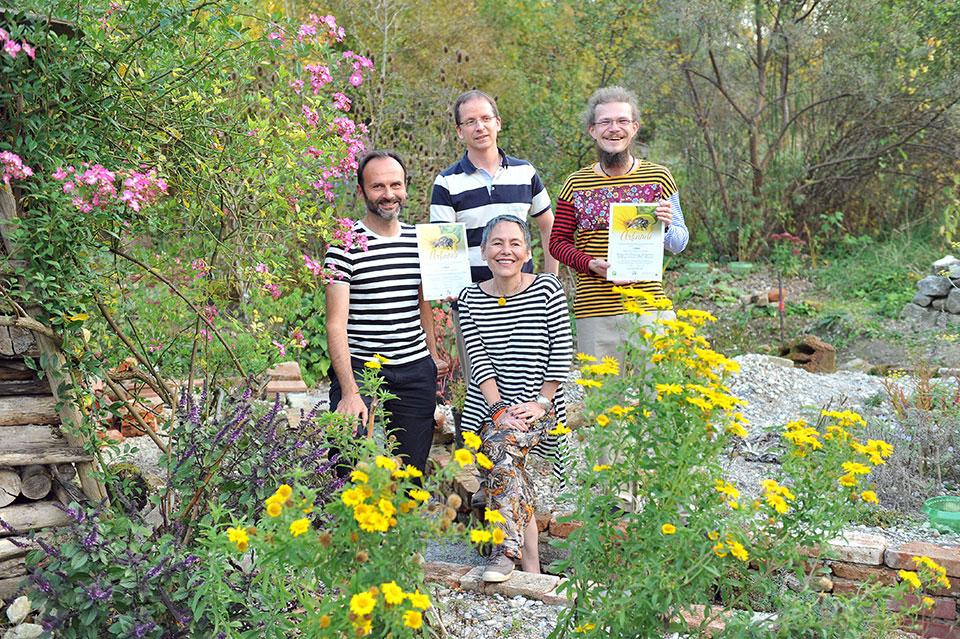 Vier Teilnehmer an dem Pflanzwettbewerb Wir tun was für Bienen! stehen inmitten einer blühenden Anlage und zeigen stolz ihre Urkunde, die ihnen bescheinigt, dass sie etwas gegen das Bienensterben unternommen haben.