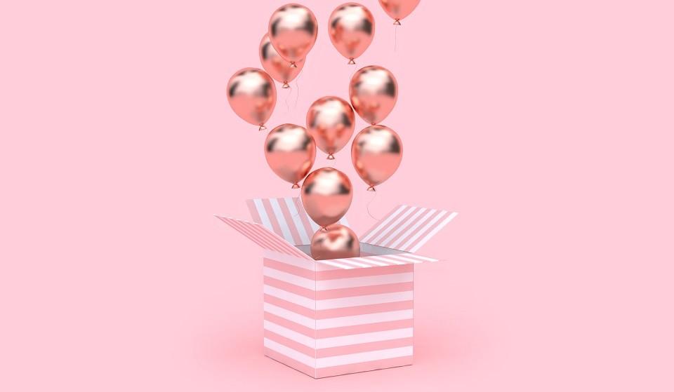 Rosegoldene Luftballons mit metallischem Glanz steigen aus einer rosa-weiß gestreiften Box hinauf.