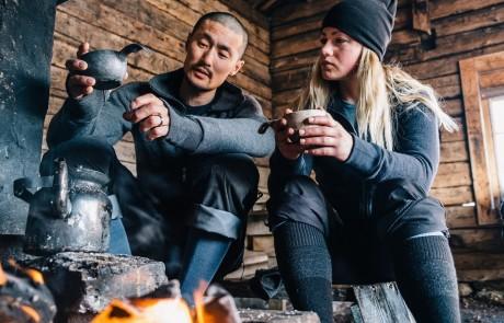Ein Paar kocht an einer Feuerstelle in einer Berghütte Wasser für einen Tee und trägt dabei Outdoor-Mode von Woolpower.