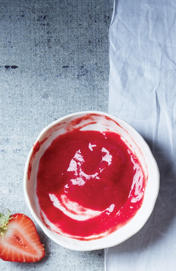 Leuchtend rote Edbeermarmelade mit Chiasamen wurde in einer kleinen, weißen Schüssel von oben fotografiert.