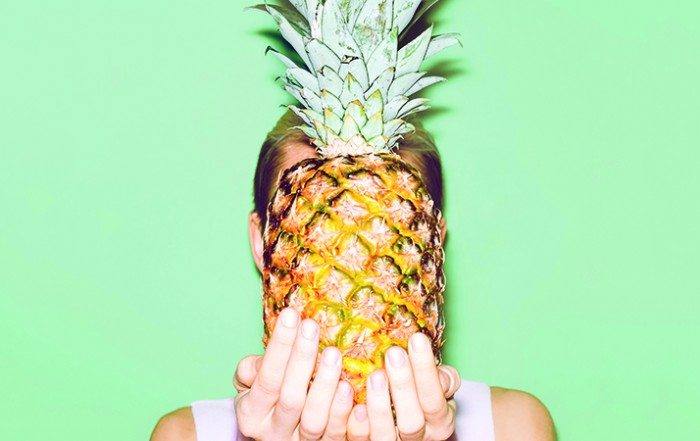 Frau hält eine Ananas vor ihr Gesicht