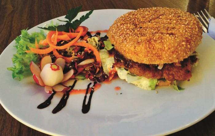 Veganger Burger vom Restaurant Falscher Hase in Dresdenmit frischer Beilage auf einem weißen Teller angerichtet.