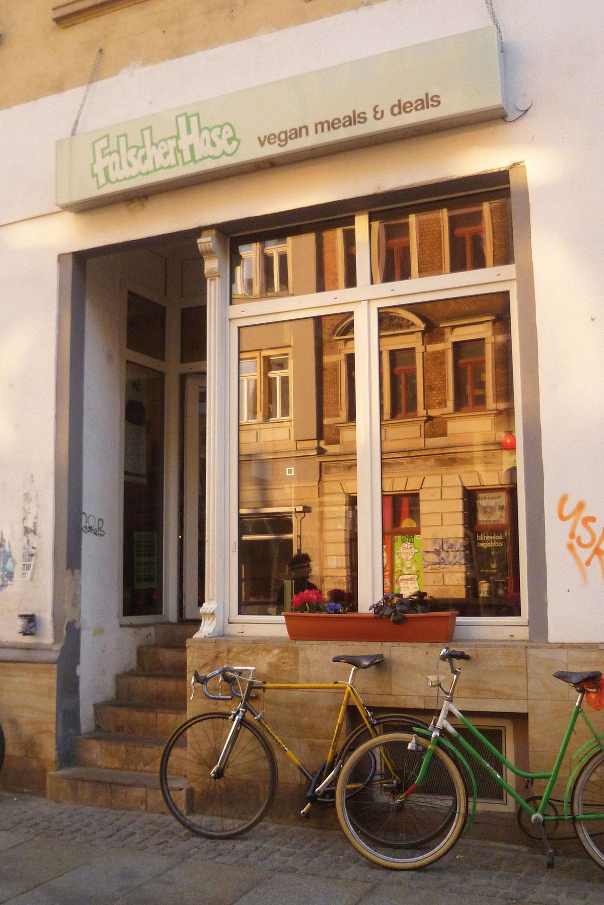 In der Fensterscheibe, vor der ein Fahrrad steht, des Dresdner Restaurants Falscher Hase reflektiert der rote Sonnenuntergang.