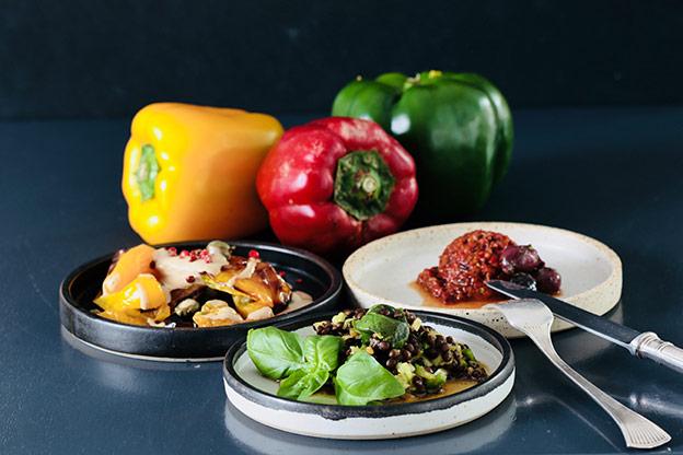 Die drei veganen Antipasti aus Paprika sind auf kleinen, flachen Tellern angerichtet und im Hintergrund sind Paprikafrüchte in den Farben Gelb, Rot und Grün zu sehen, die je für eine Antipasti-Zubereitung stehen.