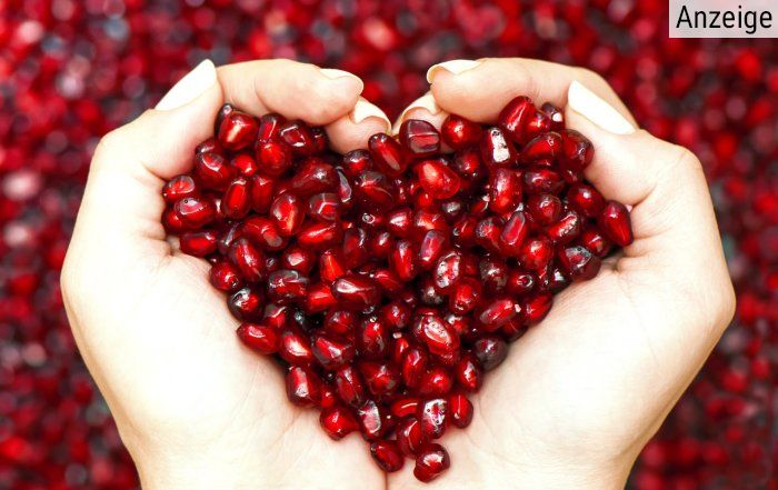 Aus Grantapfelkeren mit Händen geformtes Herz