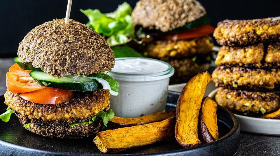 Ein veganer Burger auf einem schwarzen Teller mit Süßkartoffelpommes und veganem Dip.