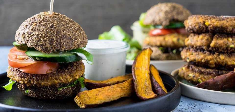 Neben selbstgemachten Süßkartoffelpommes und veganen Burgerpattys steht ein firsch zubereiteter veganer Burger mit Tomaten, Salat und Gurke.
