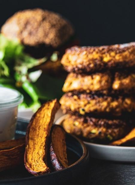 Mehrere Burgerpatties zu eine, kleinen Turm gestapelt dtehen bereit auf einem Teller, um mit einem veganen Burger Brötchen zu einem leckereren Burger ohne tierische Produktezu werden.