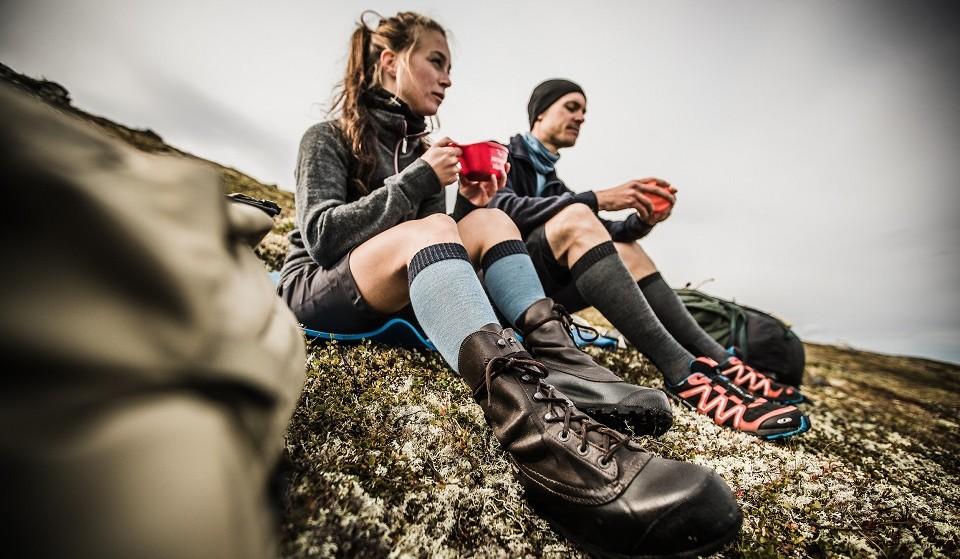Zwei Wanderer tragen Outdoorbekleidung von Woolpower und machen Rast mir einer Tasse Tee auf einer Felsplatte in den Bergen.