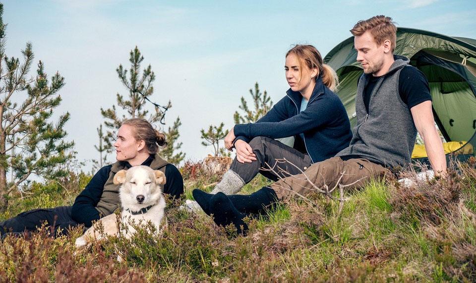 Auf einer grünen Bergwiese sitzen drei Wanderer und ein Hund in Funktionskleidung von Woolpower vor einem Zelt und betrachten die Landschaft.