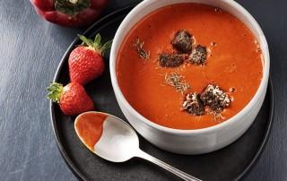 Die rote Suppe mit dunklen Croutons wird in einer weißer Suppenschale auf einem anthrazitfarbenen Teller angerichtet und mit frischen Erdbeeren garniert, sodass ein kontrastreiches Farbenspiel auf dem Tisch entsteht.