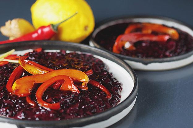 Auf einem weißen Teller leuchtet das dunkelrote Risotto, garniert mit roten Paprikastreifen, und erinnert im ersten Moment durch seinen Glanz an Granatapfelkerne.