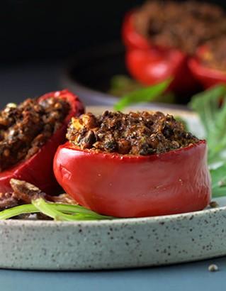 Die veganen, roten gefüllte Paprika mit Walnuss, Tofu und Kräutercreme wurden mit grünem Rucola angerichtet, sodass es auf dem Teller ein schönes Farbspiel ergibt.