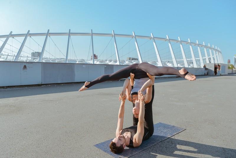 Auf einer blauen Yogamatte zeigt das Pärchen die Acro-Yoga-Figur Straddle Bat, bei der die Basis die Beine senkrecht in die Luft streckt und auf den Füßen den Flyer balanciert, der mit dem Kopf nach unten einen Spagat in der Luft macht.