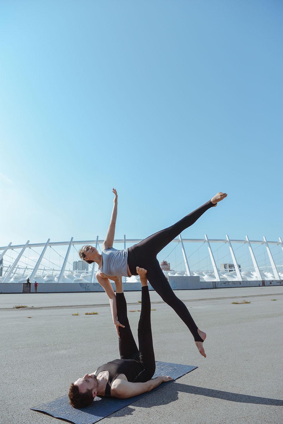 Ein Paar zeigen unter freiem Himmel und auf einer blauen Yogamatte die Figur Cartwheel aus dem Acroyoga, bei der der Mann seine Beine senkrecht in die Luft streckt und die Frau in seitlich mit gespreizeten Beinen uaf seinen Füßen balanciert.