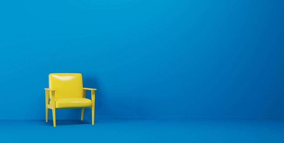 Ein gelber Stuhl im Design der 70s steht in einem blauen Raum.