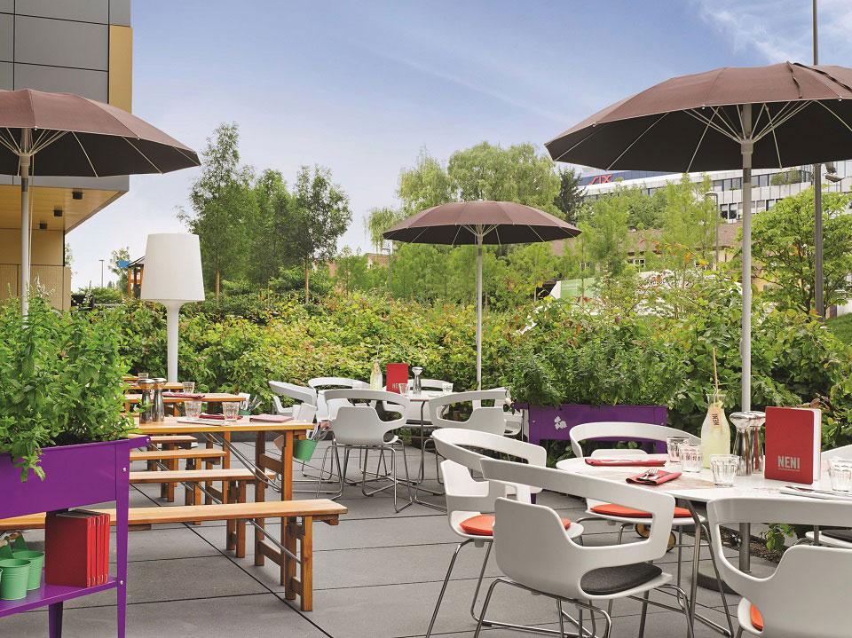 Auf de grünen Terasse des hoteleigenen Restaurants Neni im 25hours-Hotel kann man gut essen und danach gleich weiter in belebte Bahnhofsstraße in Zürich.
