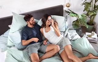 Ein junges Paar liegt in bequemen Shorty-Pyjamas im Bett und lacht.