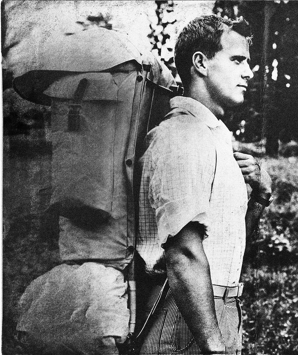 Auf einer schwarz-weißen Fotografie sieht man Fjällräven-Gründer Åke Nordin mit einem schwer beladenen Rucksack in der Natur.
