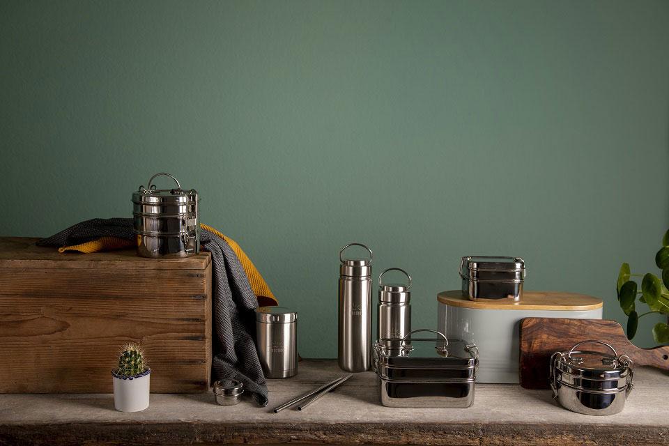Ein Teil der Eco Brotbox Produkte stehen auf einer Anrichte vor einer dunkelgrün gestrichenen Wand inmitten von eingetopften Pflanzen und anderen nachhaltigen Haushaltsartikeln.