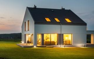 In der Abenddämmerung steht ein Einfamilienhaus, in dem gerade Lichter eingeschaltet wurden, die eine gemütliche Stimmung verbreiten und die Effizienz eines Smart Home von Gigaset verdeutlichen.