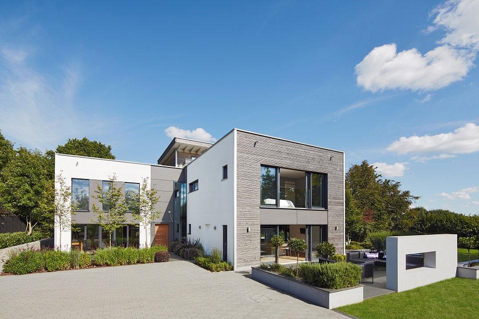 Die moderne, würfelähnliche Architektur harmoniert mit den natürlichen Baumaterialen, die Baufritz bei diesem Wohnobjekt in Großbrittanien verwendet hat.