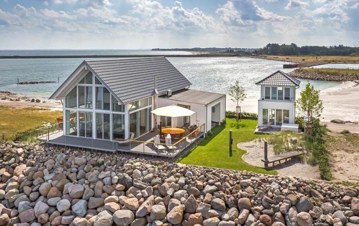 An einem norddeutschen Strand blickt man von einem Steindamm auf das ökologische Haus von Baufritz, dessen Südseite aus Glas besteht und dadurch sehr lichtdurchlässig ist.