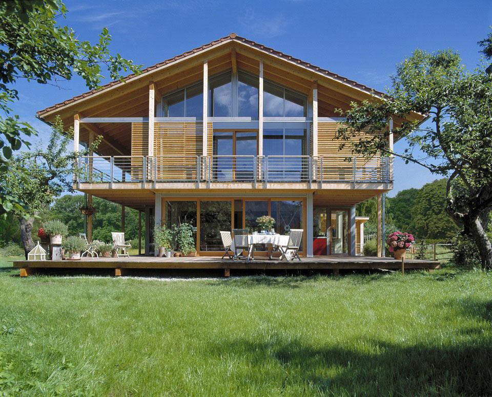 Das abgebildetete Haus von Baufritz hat ein Spitzdach und eine zum Garten zeigende Glasfront, die in Kombination mit der hellen Holzfassade modern und zeitlos wirkt.