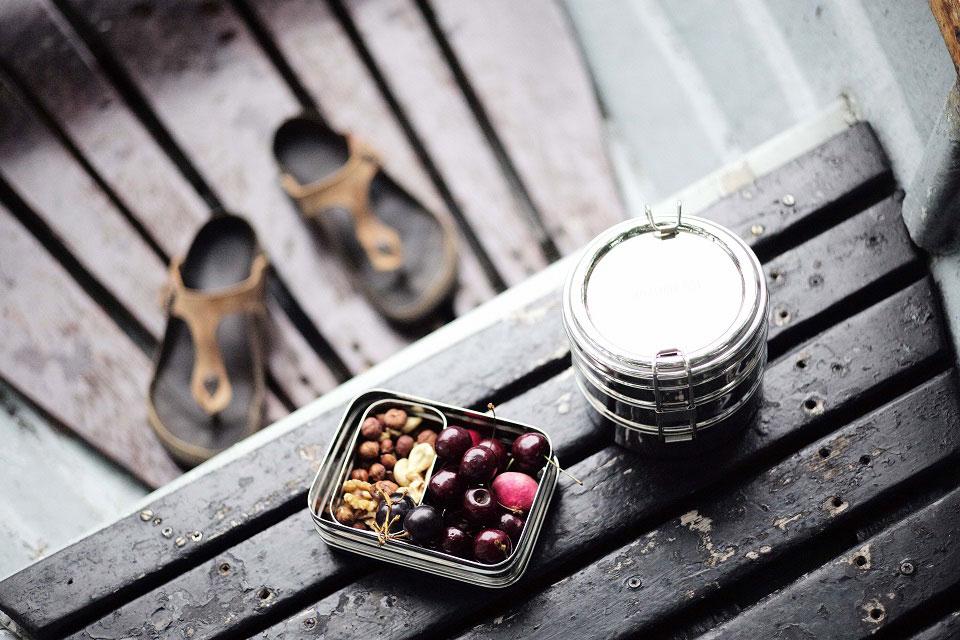 Aus der Vogelperspektive sieht man eine geöffnete ECO Brotbox mit frischen Beeren gefüllt und eine runde, geschlossene Bentobox aus Edelstahl auf einem Tisch aus Holzbalken und im Hintergrund erkennt man braune Zehensandalen von Biorkenstock, die zeigen, dass diese Aufnahme einen Snack während eines Ausflugs zeigt.