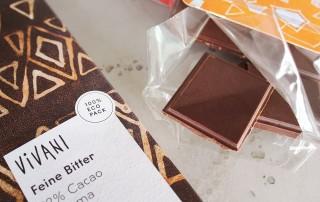 Neben einer angebrochenen Schokoladentafel der nachhaltigen Marke Vivani liegt eine verschlossene Tafel der Sorte Feine Bitter, die zu 92 Prozent aus Cacao aus Panama besteht, und auf deren dunkelbrauner, mit goldenen Elementen verzierten Verpackung ein Etikett auf die zu 100 Prozent ökologische Verpackung hinweist.