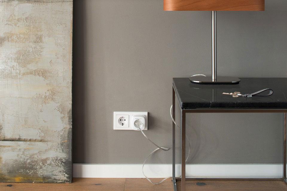 Der Ausschnitt eines modern eingerichteten Wohnraums zeigt eine intelligente Steckdose, an der eine Lampe angeschlossen ist, deren Stromverbrauch nun nach Bedarf bequem per App gesteuert werden kann.
