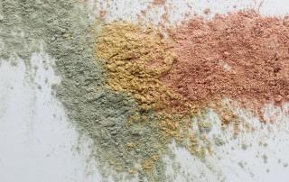 Drei unterschiedle Arten der Heilerde liegen in Pulverform auf einem weißen Untergrund ergeben so einen schönen pastelligen Farbverlauf von grün über gelb bis hin zu rot.