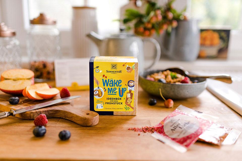 Die SONNENTOR Ideenbox steht auf einer Küchenanrichte, umgeben von Apfelscheiben und frischen Beeren.