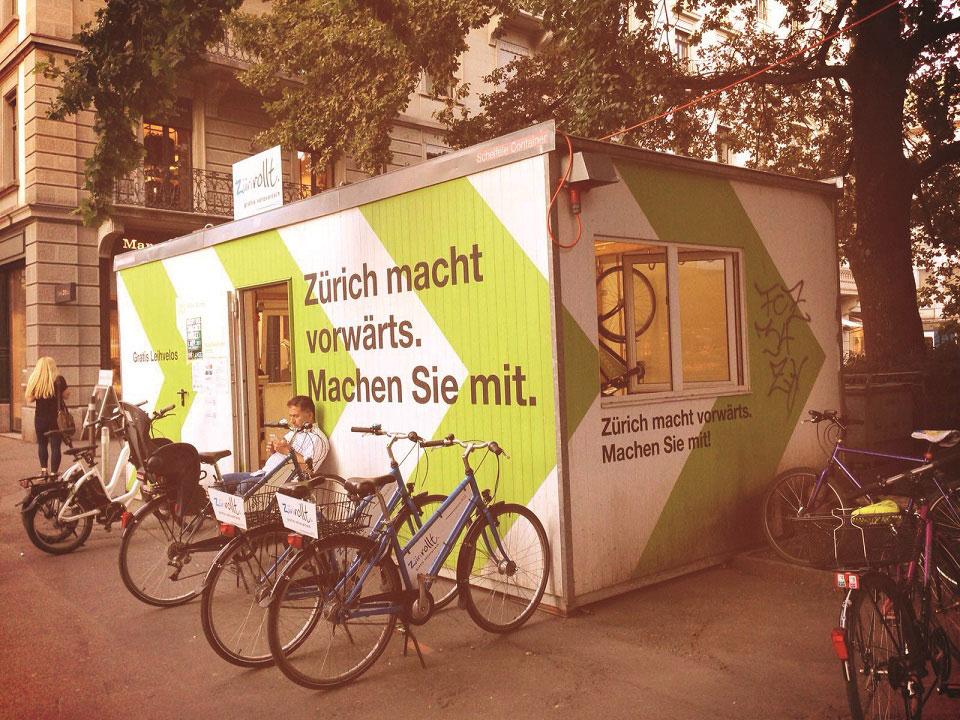 Mehrere Fahrräder stehen an einer Station des Projekts Züri Rollt vor dem Container bereit, um Touristen und EInheimische durch die Schweizerische Hauptstadt zu erkunden.