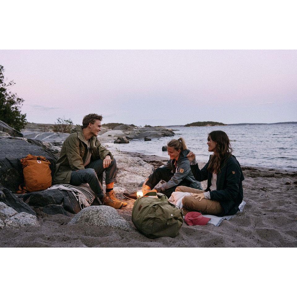 Ein junger Mann sitzt mit zwei jungen Frauen, bekleidet und ausgerüstet mit Jacken sowei Rucksäcken und Taschen von Fjällräven, sitzen um ein Camping-Licht, das dem Lager am Strand mit Meer im Hintergrund eine romantische und zugleich abenteuerliche Atmosphäre verleiht.