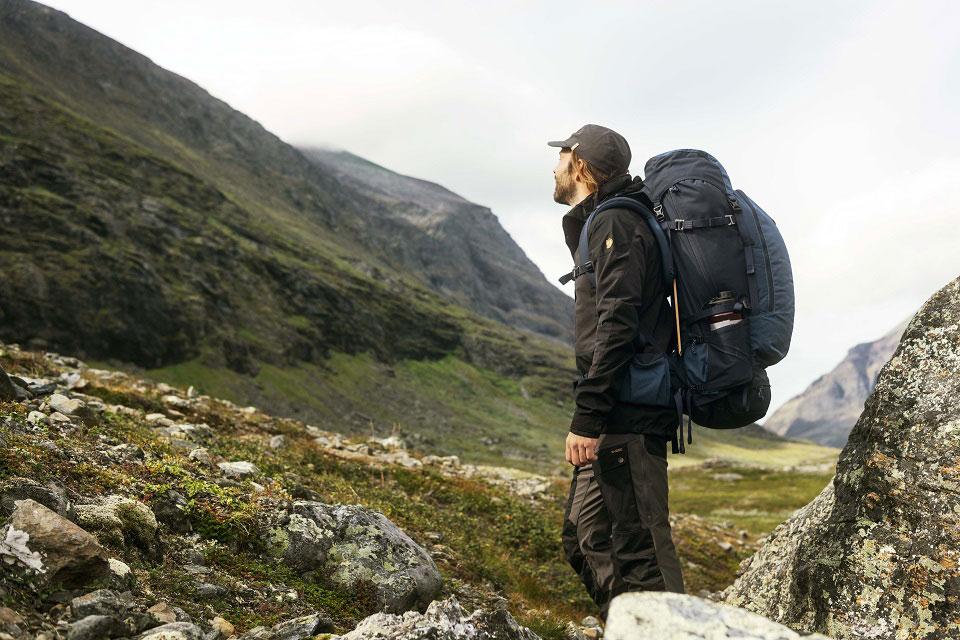 In hochwertiger Ausrüstung, von Wanderhose, Wanderrucksack, Schirmmütze bis zur wetterfesten Jacke von der schwedischen Marke Fjällräven erkundet ein Wanderer die Natur in einer grünen, schwedischen Bergregion.