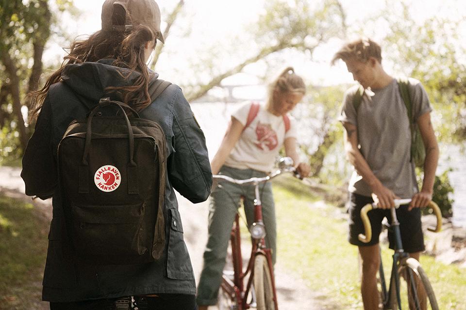 Drei junge Menschen, die mit der neuen Fjällräven Kollektion gekleidet sind, einer von ihnen trägt den berühmten Kanken-Rucksack bei sich, machen während einer Fahrrad-Tour Halt in der Natur, wo grüne Bäume Schatten spenden und ein Bach im Hintergrund rauschend vorbei fließt.