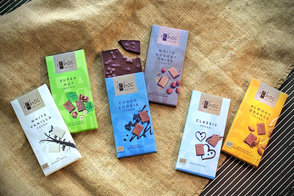 Die sechs veganen Schokoladensorten von iChoc liegen auf einem hellbraunen Jutestoff, der die knalligbunten Verpackungen, die mit mineralfreier Biofarbe bedruckt werden, besonders zur Geltung bringt.