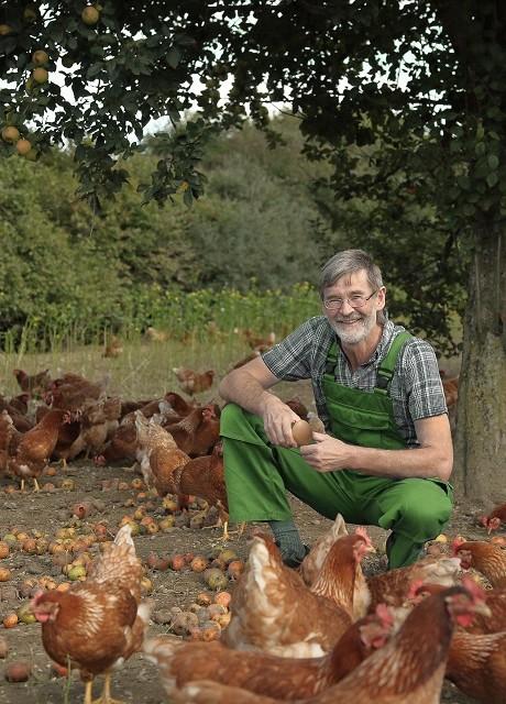 Biobauer Sepp kniet hier inmitten seiner Hühner im grünen Außenbereich. Er ist der Futterexperte von Die Biohennen.