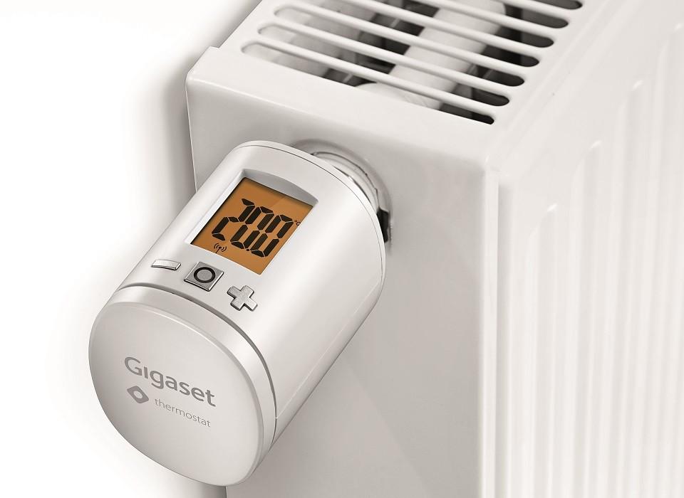 Das Gigaset Smart Thermostat in Nahaufnahme an einer Heizung verdeutlicht die vielen praktischen Funktionen, die ein effizientes, sparsarmes und trotzdem komfortables Nutzen der Energie ermöglichen.