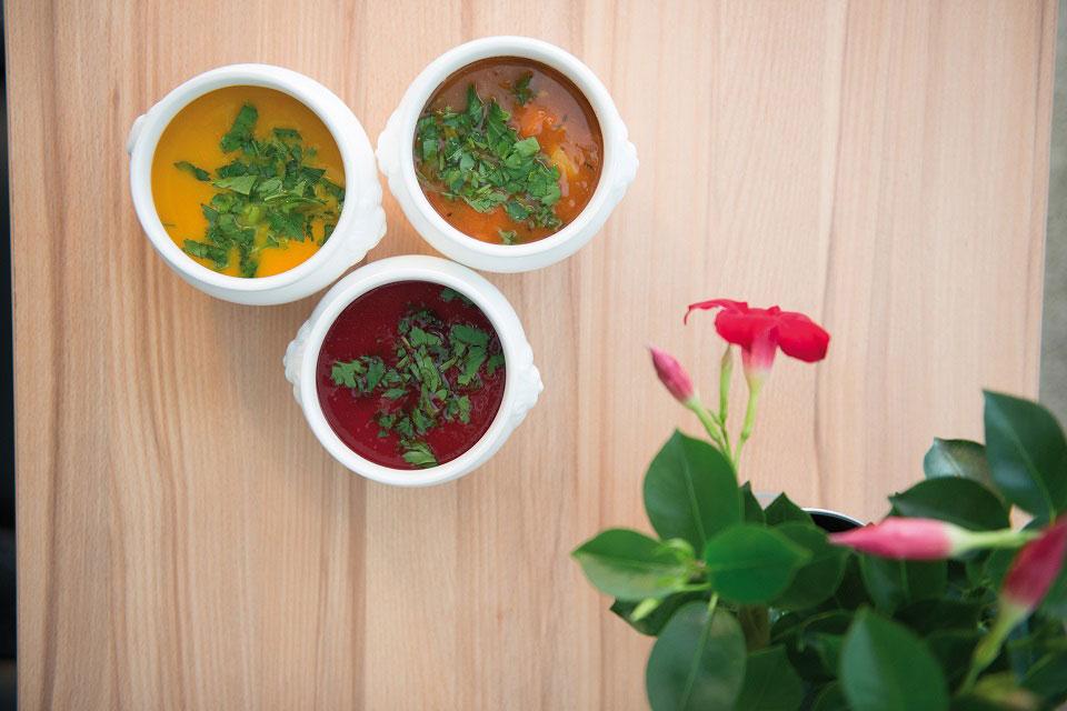 Drei frisch zubereitete Suppen mit unterschiedlicher Färbung von Gelb über Orange bis hin zu Rot wurden im Restaurant Saint Louis in Köln zusätzlich mit grüner Petersilie garniert.
