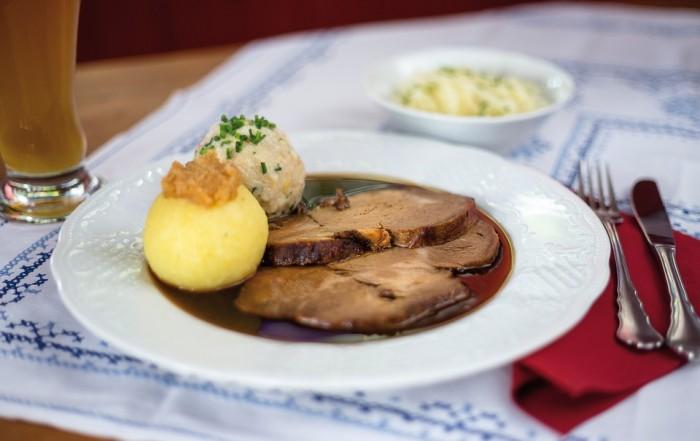 Der hausgmachte Schweinebraten wird im Münchner Restaurant Klinglwirt in einem tiefen weißen Teller mit reichlich dunkler Soße, einem Kartoffelknödel und einem Semmelknödel sowie mit Krautsalat serviert.