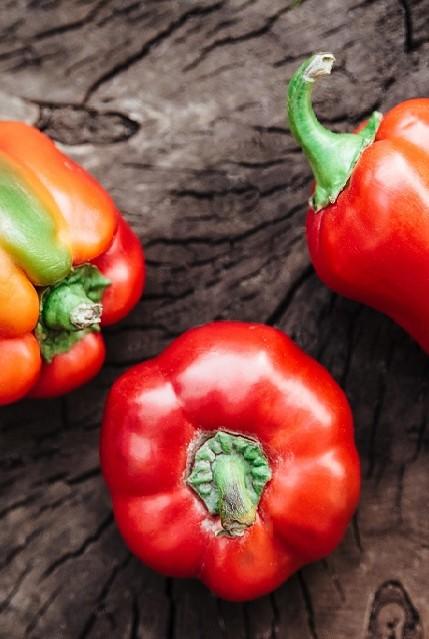 Drei rote Paprika liegen auf einem dunklen Holztisch.