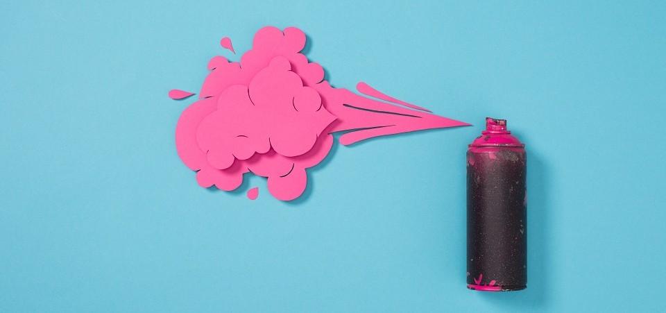 Auf einem blauen Hintergrund liegt eine schwarze Farbdose mit Sprühaufsatz, aus dem eine pinke Wolke kommt.