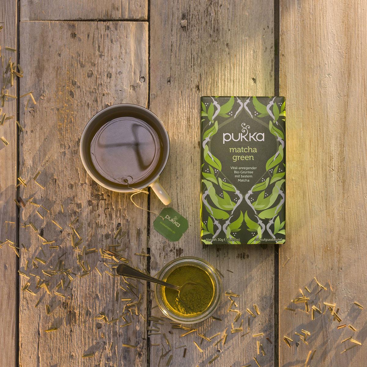 Eine Teetasse mit dem Matcha Green Tee von Pukka steht auf einem hölzernenen Untergrund neben einem Glas mit grünem Matchapulver und der für Pukka Tees typisch auffällig designten Verpackung.