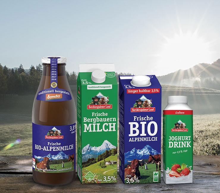 Vier Biomilchprodukte von der Molkerei Berchtesgadener Land wurden auf einem holzigen Untergrund vor einer Alpenkulisse platziert und repräsentieren das vielseitige Sortiment des naturnahen Betriebs.