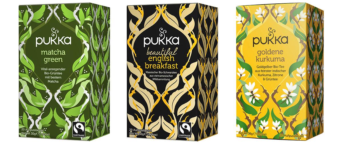 Drei bunte Packungen verschiedener Pukka-Tees stehen aufgereiht nebeneinander. In der grünen Verpackung befindet sich Grüner Matcha, der English Breakfast Tee ist schwarz und die Sorte Goldener Kurkuma gelb verpackt.