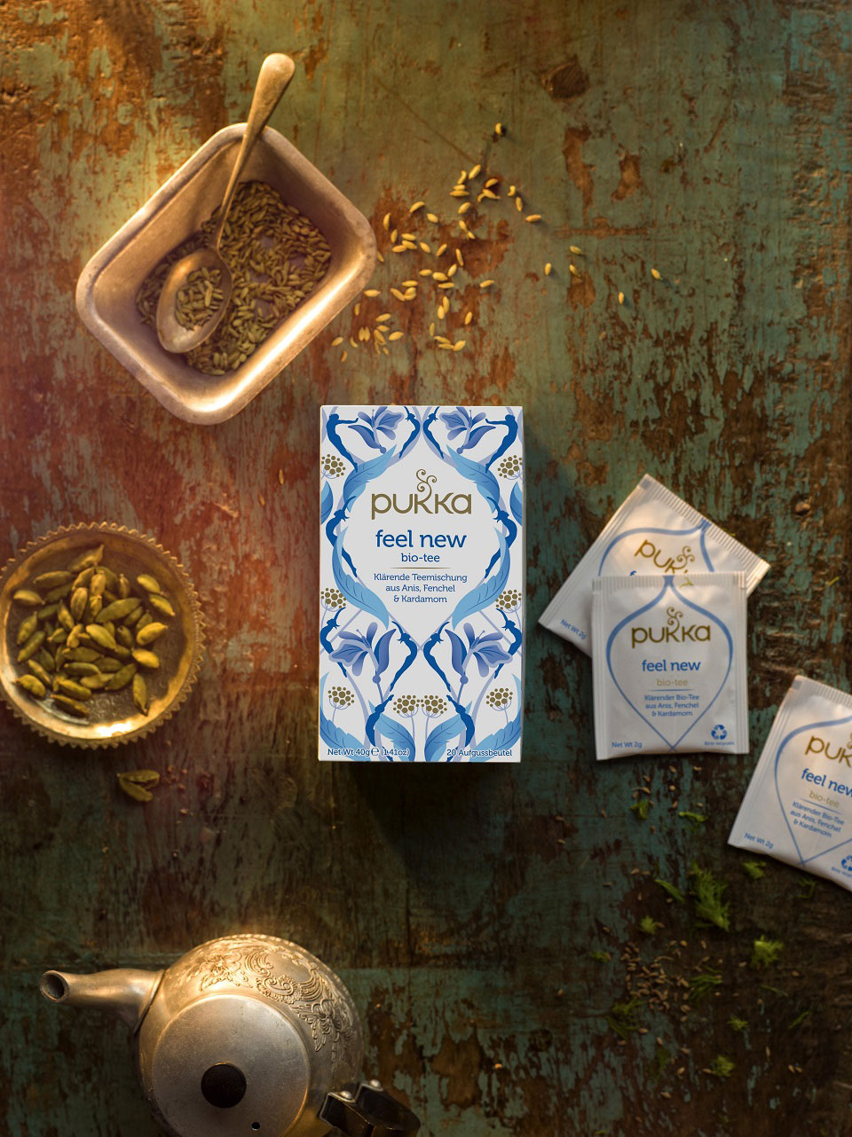 Die helle Packung des Pukka Feel New-Tees umgeben von Teebeutelverpackungen und den Zutaten des Kräutertees.